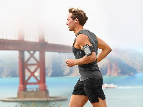 Running man - male runner in San Francisco listening to music on smart phone. Sporty fit young man jogging by San Francisco Bay and Golden Gate Bridge. Jogger listening to training music on smartphone